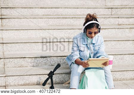 Young Woman In Headphones Sitting On Steps And Watching New Episode Of Popular Show On Tablet Comput