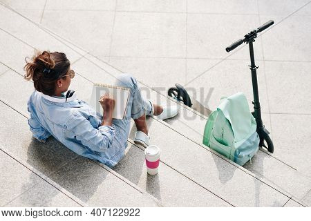 Creative Young Woman Sitting On Steps With Cup Of Take Out Coffee And Drawing Sketch In Sketchbook