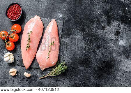 Raw Turkey Steaks. Breast Fillet. Black Background. Top View. Copy Space