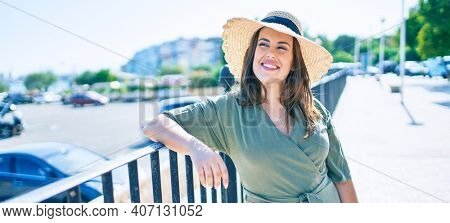 Young hispanic woman on vacation smiling happy leaning on balustrade at street of city