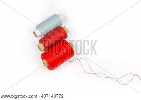 Spools Of Threads Different Colors And Self-threading Hand Sewing Needle With A Tucked Red Thread On