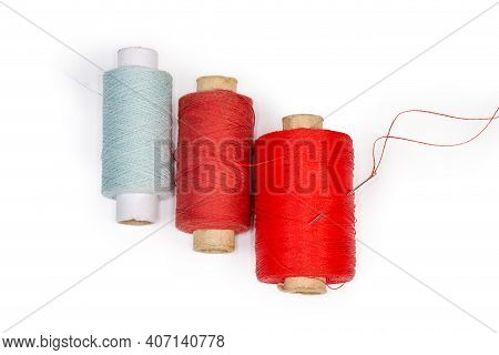 Spools Of Threads Different Colors And Self-threading Hand Sewing Needle With A Tucked Red Thread, T