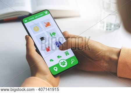 Woman Using Mobile Phone App To Order Food Delivery