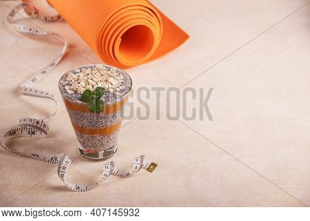 Healthy Lifestyle Concept. Healthy Chia And Yogurt Dessert And Yoga Mat On A Light Table
