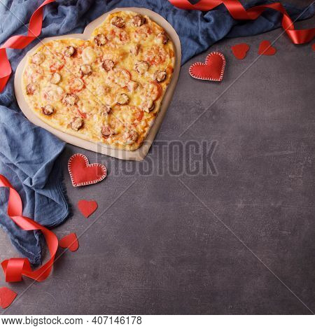 Heart Shaped Pipperoni Pizza For Valentine's Day On A Black Background. Top View. Place For Your Tex