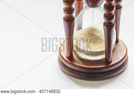 Wooden Vintage Hourglass Close Up. Sand Passing Through The Glass Bulbs Of An Hourglass Measuring Th