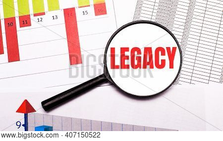 On The Desktop, Graphs, Reports, A Magnifying Glass With The Inscription Legacy. Business Concept