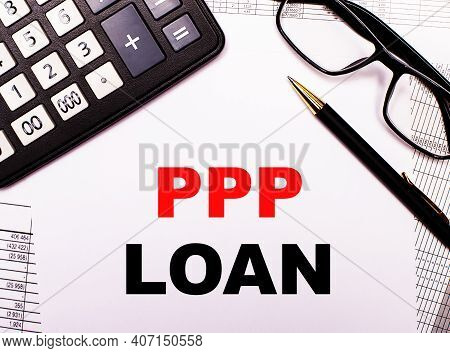 On The Reports There Is A Calculator, Glasses, A Pen And A Notebook With The Inscription Ppp Paychec