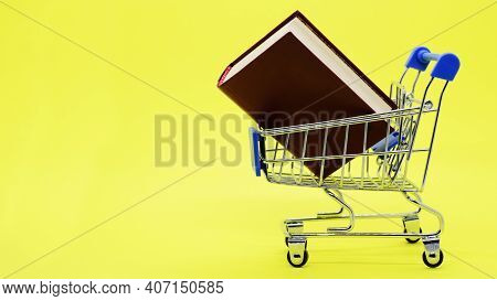 Metal Supermarket Trolley With Thick Book On Yellow Background. Space For Text. Concept: Purchase Of