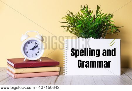 Spelling And Grammar Is Written In A Notebook Next To A Green Plant And A White Alarm Clock, Which S