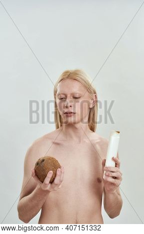 Young Caucasian Man With Long Blond Hair Holding Shampoo Bottle And Coconut In Hand While Standing O