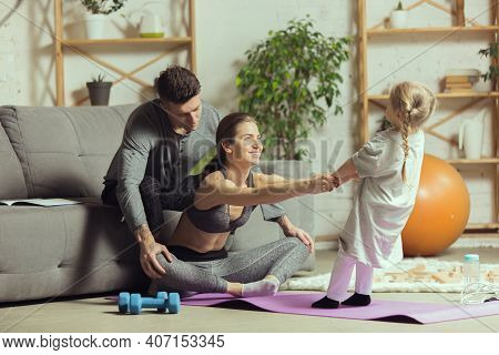 Doing Yoga With Daughter. Young Woman Exercising Fitness, Aerobic, Yoga At Home, Sporty Lifestyle An