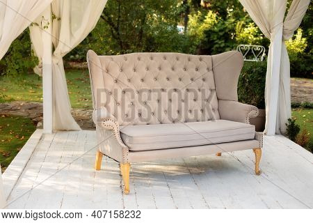 In Garden There Is Podium On Which Sofa In Style Of Provence Or Rustic. Summer Gazebo With Flowing W