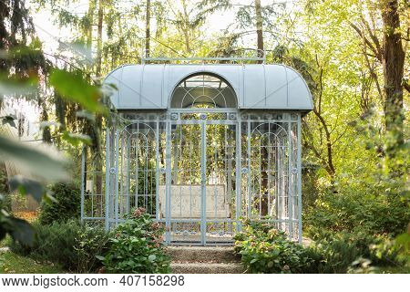 Wrought Metal Gazebo In Summer Garden. Flowers In Pots Near Porch. Sofa In Spring Gazebo. Large Iron