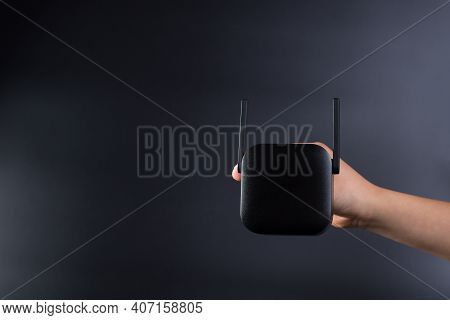 Hand Holding Black Wifi Amplifier, On Black Background With Copy Space.