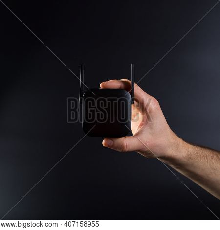 Hand Connecting Black Wifi Amplifier  To Electrical Outlet, On Black Background.