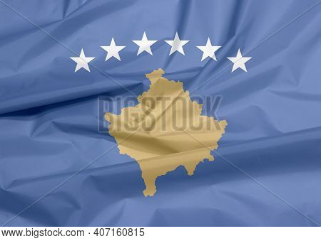 Fabric Flag Of Kosovo. Crease Of Kosovo Flag Background, A Blue Field Charged With A Map Of Kosovo I