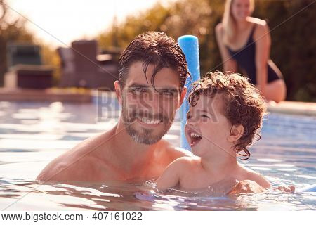 Family In Outdoor Pool On Summer Vacation Teaching Son To Swim With Noodle Swimming Aid