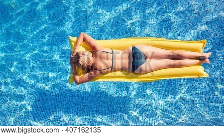 Overhead Shot Of Woman In Bikini Floating On Air Bed On Summer Vacation In Outdoor Swimming Pool