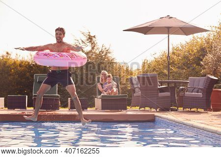 Father With Inflatable Ring Jumps Into Outdoor Pool On Summer Vacation Watched By Mother And Son
