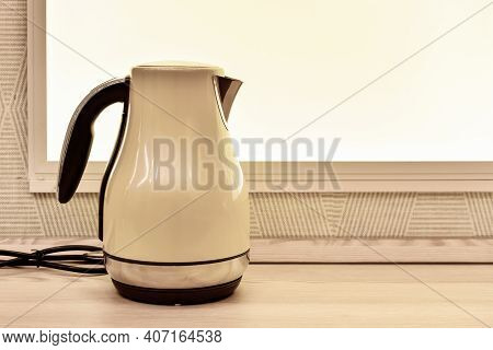 Electric Kettle On  Background Of Window In  Kitchen. Kitchen Appliances. Empty Space For Text. Illu