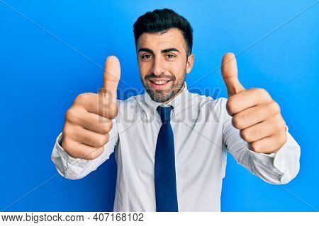 Young hispanic man wearing business clothes approving doing positive gesture with hand, thumbs up smiling and happy for success. winner gesture.