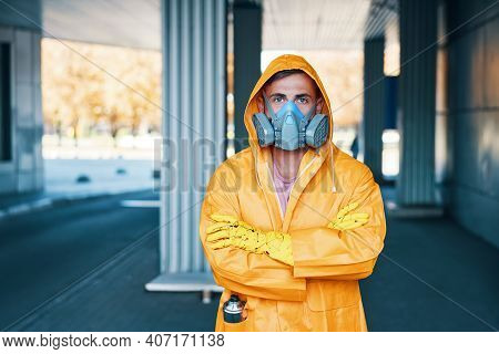 Close Up Portrait Of Young Man In Respirator Mask And Yellow Raincoat Posing On The Street Looking A