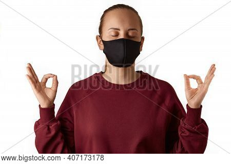 Yoga Time. Young European Woman Wears Face Mask And Burgundy Sweatshirt, Practices Yoga, Holds Hands