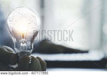 Businessman Holding Glowing Lightbulb With Brain And Using Computer Laptop To Input Business Strateg