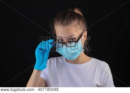 Woman In A Median Face Mask, Gloves And Glasses On A Black Background.