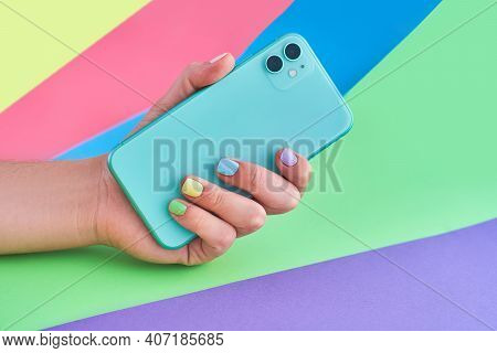 Female Hands With Color Manicure Holds Green Mint Colored Smartphone With Dual Lenses On A Bright Co