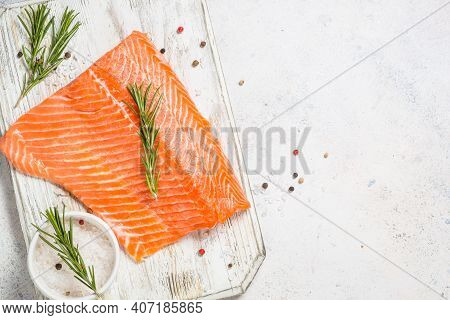 Salmon Fillet With Sea Salt And Rosemary. Raw Fish. Top View At White Table.