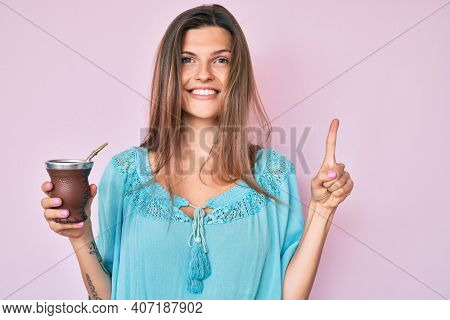 Beautiful caucasian woman drinking mate infusion smiling with an idea or question pointing finger with happy face, number one