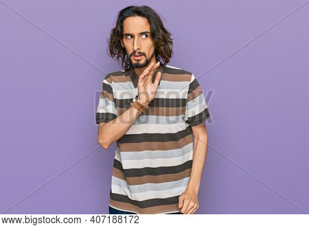 Young hispanic man wearing casual clothes hand on mouth telling secret rumor, whispering malicious talk conversation