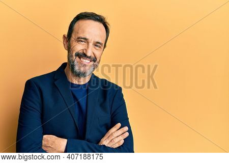 Middle age hispanic man wearing business clothes happy face smiling with crossed arms looking at the camera. positive person.