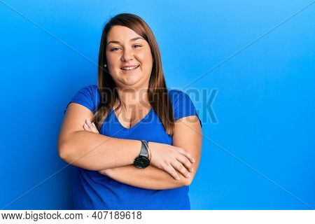 Beautiful brunette plus size woman wearing casual blue t shirt happy face smiling with crossed arms looking at the camera. positive person.