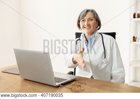 Senior Old Female Doctor With Stethoscope Wearing Lab Coat Sitting At The Desk With Laptop, Welcomin