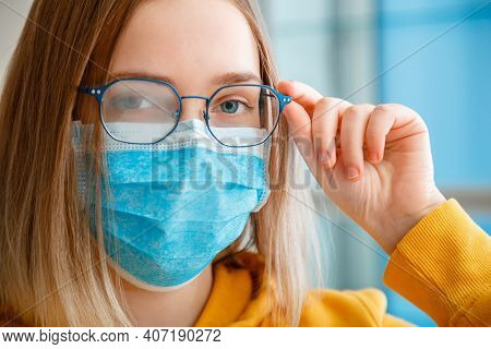 Foggy Glasses Wearing On Young Woman. Close Up Portrait. Teenager Girl In Blue Medical Protective Fa