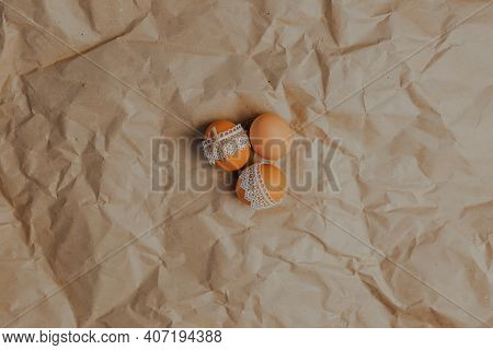 Decorating Easter Eggs On Kraft Paper With Lace And Rope. Three Easter Eggs On Kraft Paper Backgroun