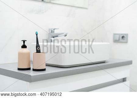 Oral Care And Dental Hygiene Concept. Electric Toothbrush In Cup And Soap Dispenser Bottle Near Basi