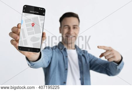 Cheerful Man Showing Cellphone With Mobile Navigation Application Standing Over White Studio Backgro