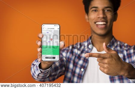 Cheerful African Man Showing Cellphone With Navigation Application Smiling To Camera Standing Over O