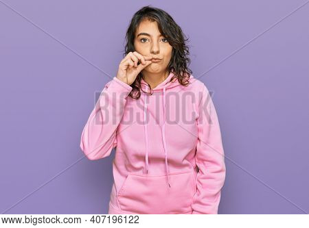 Young hispanic woman wearing casual sweatshirt mouth and lips shut as zip with fingers. secret and silent, taboo talking