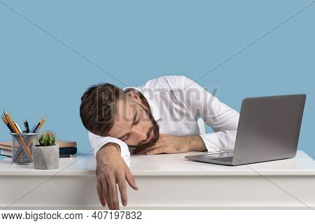 Exhausted Young Businessman Sleeping On His Desk, Tired Of Overworking On Blue Studio Background, Co