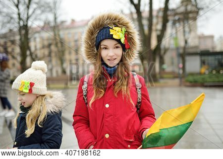 Two Adorable Young Sisters Celebrating Lithuanian Independence Day Holding Lithuanian Flags In Vilni