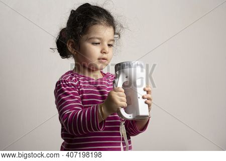 Little Girl Playing With A Torch Light Childhood Curiosity Concept