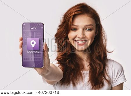 Happy Red-haired Woman Showing Smartphone With Mobile Navigation App Posing Standing Over White Stud
