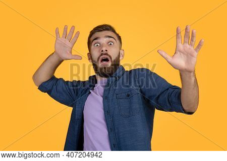 Scared Caucasian Man Making Frightened Gesture With His Hands, Trying To Defend Himself On Orange St