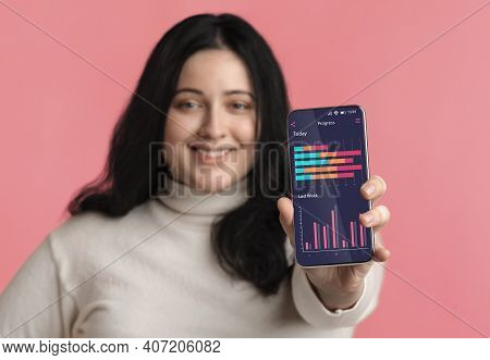 Weightloss Progress App. Plus Size Woman Showing Application On Smartphone For Activity Tracking Wit