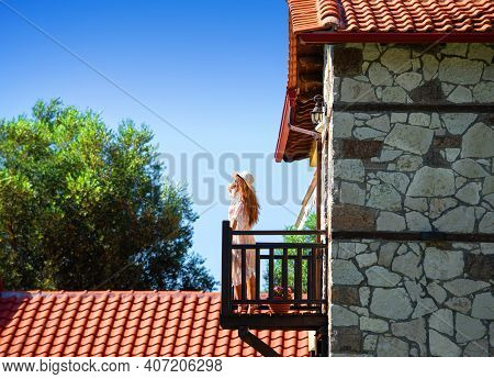 Side View Of Young Woman Standing On Wooden Balcony Of Old Cobble Stone House With Red Tile Roof In